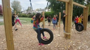 Photo courtesy of Dearborn Heights Montessori Center. Students at DHMC use the newly completed low ropes course during physical education to learn team building skills.