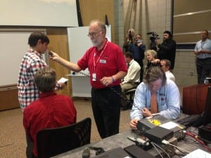 Photo by Zeinab Najm. Student Ibrahim Ahmad (left), 13, and Ford Amateur Radio League volunteer Larry Koziel ask NASA astronaut Kjell Lindgren a question with the help of Dearborn Public Schools Media Tech Specialist Gordon Scannell at the Michael Berry Center Oct. 27.
