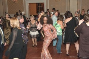 """Photo courtesy of Besek Photography. Black Tie & Tails guests dance the night away to 1970s-era disco music as part of the """"Dog Days of Disco"""" theme."""