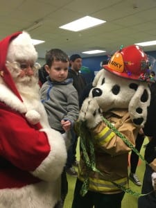 Photo by Zeinab Najm. Santa Claus, 4-year-old Mason Maier and Sparky the Fire Dog await the arrival of Maier's Christmas gift from the Dearborn Firefighters at the Beaumont Center for Exceptional Families Dec. 11.