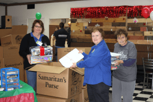 Photo by Sue Suchyta. Denise Miller (left) of Allen Park, and Dearborn residents Janet Gleichauf and Sandra Nader help pack shipping boxes with plastic shoe boxes filled with gifts for children at a Samaritan's Purse Operation Christmas Child drop-off center in Dearborn. For more information, go to samaritanspurse.org.