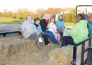 Photo by Sue Suchyta. Megan Dodd (left), 8, of Riverview; Emma Green, 7, of Adrian; and Riverview residents Molly Chrusciel, 19, Cecilia Alderman, 5 and Isabel Alderman, 9, get ready for a hayride Nov. 12 at Riverview Recreation Department's Fall Family Festival at Young Patriot's Park.