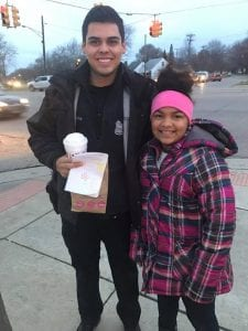 Photo by Laura Gisel. Lincoln Park Police Officer Alejandro Serna (left) received a surprise treat from Kayle Gisel Tuesday when she stopped to deliver him hot chocolate and doughnuts at the corner of Champagne and Dix while on her way to school.