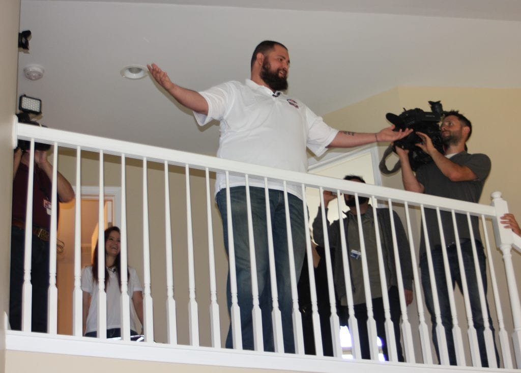 Photo by Sue Suchyta Disabled Marine Corps veteran Joshua Schroeder (center) hams it up for the press on the balcony of his new mortgage-free home in Taylor, made possible through Building Homes for Heroes and Chase Bank while his wife, Briana (second from left), laughs.