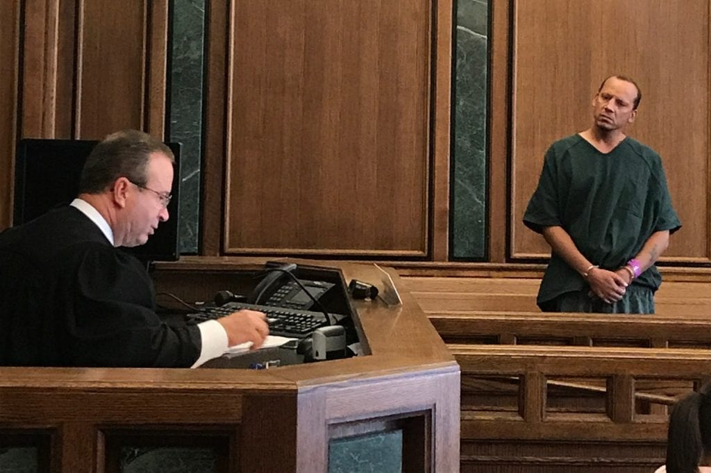 Photo by Zeinab Najm Nineteenth District Court Judge Mark Somers (left) reads multiple arson charges against Inkster resident David Cerne, accused of throwing an explosive firework into Divine Child Church during prayer service on Aug. 23.