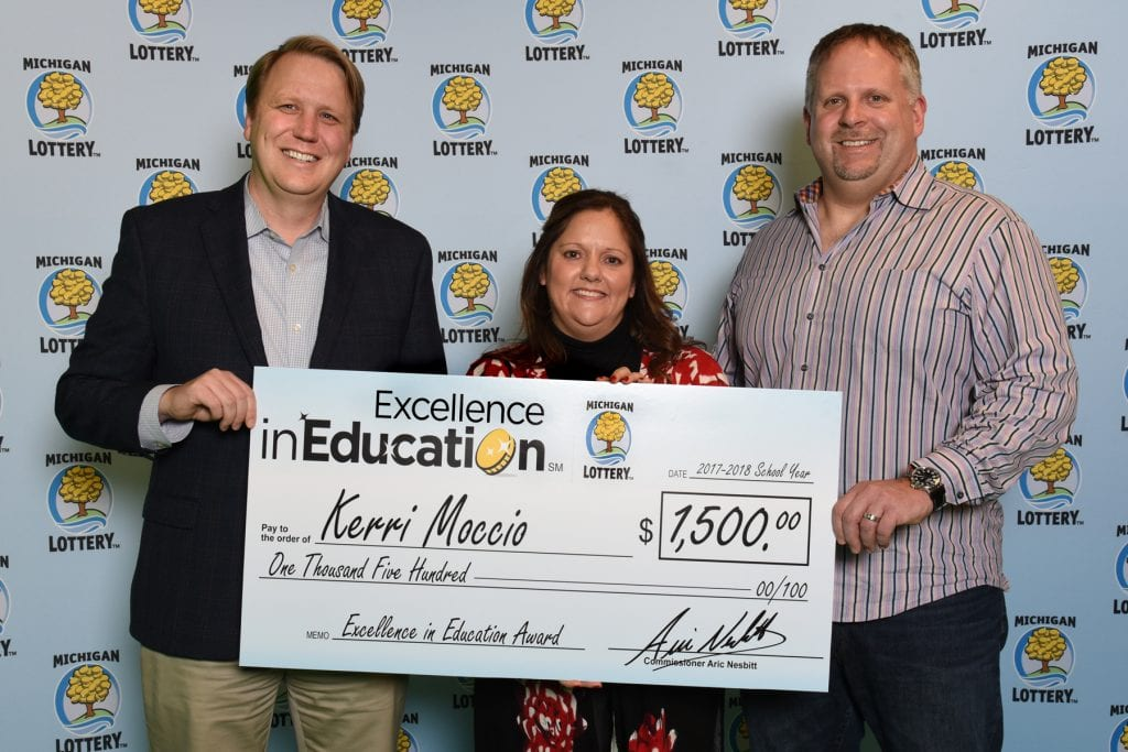 Photo courtesy of the Michigan Lottery Public Relations Division Kerri Moccio (center) and her husband, Craig (right) accepts her Excellence in Education Award from Michigan Lottery Commissioner Aric Nesbitt.