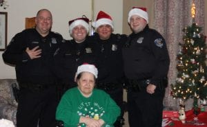 Photo by Sue Suchyta Andrea Parisi, who has mobility issues, with Taylor Police Sgt. Jeff Adamisin (left), and Officers Nick Wellman, Thomas Amross and Billy Shillingburg on Dec. 22, when the officers visited her eight days after her microwave exploded and caught fire Dec. 14.