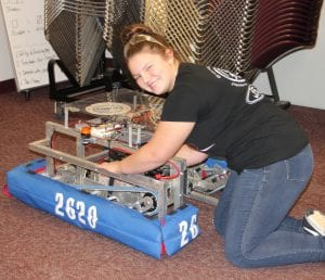 Photo by Sue Suchyta Chloe Doherty, 15, of Southgate, with the Southgate Anderson High School Robotic Team's robot at a family tech night.