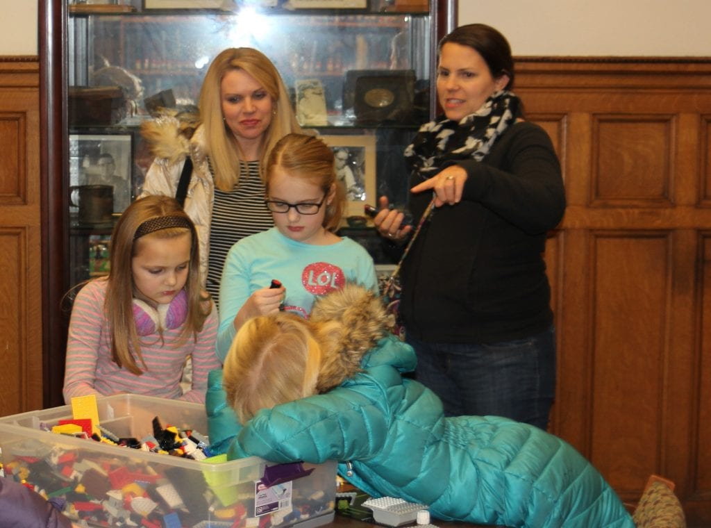 Photo by Sue Suchyta Julia Kortas, 7, dives into a Lego bin while friends Chloe (left), 7, and Claudia Kortas, 9; their mother, Karen Kortas (second from left); and Julia's mother, Erin, watch at a family tech night Jan. 12 at Bacon Memorial District Library in Wyandotte.