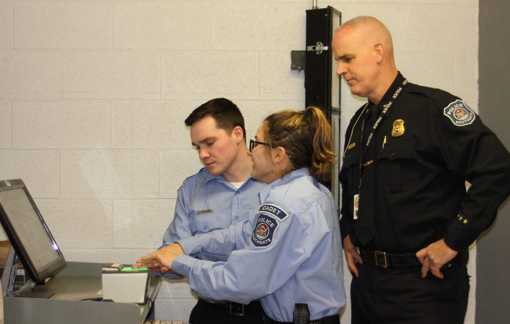 Photo by Sue Suchyta Southgate Police Cadets Jacob Bolsley (left), 22, and Alexandra Sinani, 18, learn to use the fingerprint scanner under the direction of Police Chief Brett Selby.
