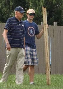 Photo courtesy of Christopher Watson Eagle Scout Christopher Watson (right) confers with a volunteer during his Eagle Scout project, the repair of a 400-foot fence for a local church.