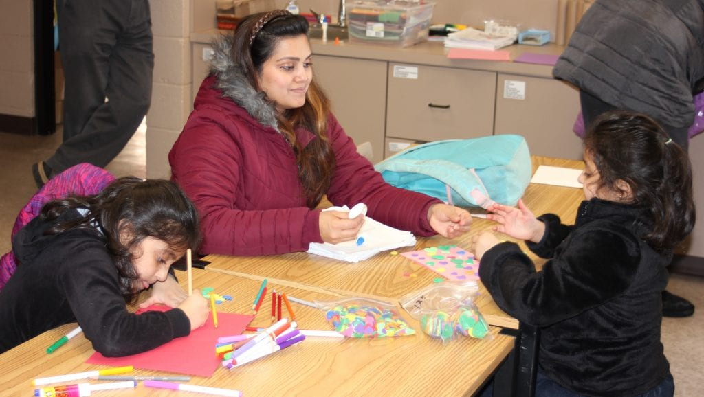 Photo by Sue Suchyta Romulus resident Areej Javaid (left), 6, makes a valentine card with her mother, Khizra, and twin sister Aroosh, 6, Feb. 12 at Southgate Veterans Memorial Library, 14680 Dix Toledo Road.