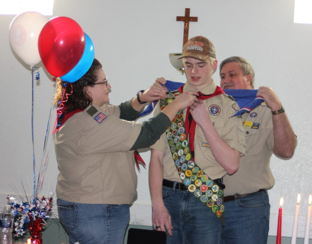 Photo by Sue Suchyta Scoutmaster Jennifer Siegel (left) helps Eagle Scout Christopher Watson prepare to wear his new Eagle Scout neckerchief, as his former scoutmaster, Raymond Champaign, helps on March 4 during Watson's Court of Honor ceremony, held at the Allen Park Knights of Columbus Hall.