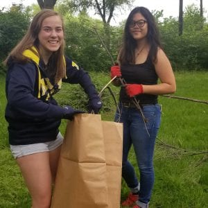Photo courtesy of Lisa Hicks-Clayton Annapolis High School Key Club members Hannah Fleenery (left) and Shaira Marquez clean up tree branches during the third annual A Day In May community service cleanup on May 26.