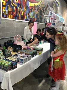 Photo by Zeinab Najm Dearborn residents Rachel Rose (left) and her daughter, Sophia, pick out figurines from exhibitor Lift Detroit during ComiqueCon in 2016.