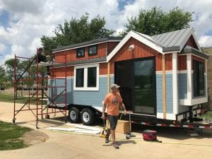 Photo by Zeinab Najm  Henry Ford College Building Science Chairman Chad Richert gathers tools to complete construction of the RE/MAX Tiny Home for Tiny Tots on June 13 at the HFC campus.