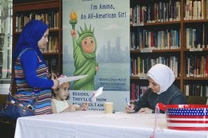 "Photo courtesy of Shayma Mustafa Author and teacher Shayma Mustafa (right) signs copies of her book ""Excuse me Ma'am, Excuse Me Sir: I'm Amina, an All-American Girl"" July 1 at the Arab American National Museum in Dearborn."