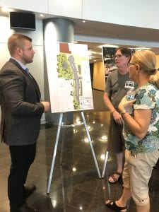 Photo by Zeinab Najm  Ford Land Project Manager James Brutton (left) explains to residents the construction details for a new ring road that is being constructed near Ford Motor Co's. Maintenance and Operation building during a community meeting on July 19.