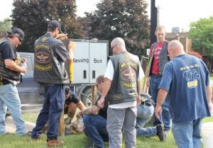 """Photo by Sue Suchyta """"Stewie"""" (second from left), checks to see if the Blessing Box is level, as other members of the Widows Sons Riding Association anchor the footings in a fast-setting concrete mix Aug. 19 at Melvindale City Hall."""