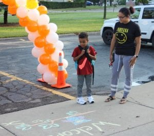 Photo by Sue Suchyta Kole Britton (left), 5, an incoming kindergartner, looks at the chalk messages on the sidewalk entrance the first day of school Sept. 4 with his mother, Kiara Britton, outside of Myers Elementary, 16201 Lauren Drive, Taylor.