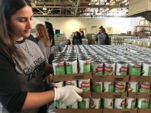 Photo by Zeinab Najm Dearborn resident and Challenge Detroit Fellow Tina Saad, 28, helps organize cans of corns during a hands-on volunteer service activity Sept. 21 at the Focus: HOPE Westside Food Center in Detroit.