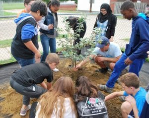 Photo courtesy of Beaumont Health Smith Middle School students help plant an apple tree outside the school on Oct. 3. Food and flower gardens are being installed outside eight Dearborn Public Schools as part of a D-SHINES wellness grant received by Beaumont Health and Healthy Dearborn.