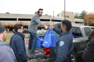Photo courtesy of Wassim Mahfouz Facebook Lebanese American Heritage Club Executive Director Wassim Mahfouz (second from left) and a Dearborn Police Explorer load bags filled with foods into a truck for local families in need during the LAHC's 13th annual Turkey Drive Nov. 17.