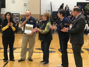 Photo by Zeinab Najm  Guy DelGiudice (second from left), longtime coach at Fordson High School, tears up during the Nov. 29 court dedication ceremony as Principal Heyam Alcodray (left), DelGiudice's wife Janet, and school board Trustees Mary Petlichkoff and James Thorpe applaud.