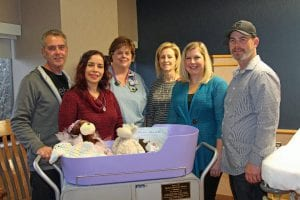 Photo courtesy of Henry Ford Wyandotte Hospital Women and Children's Health nurse Andrea Carlson and nurse Manager Mary DeSana (center) accept the donation of a Caring Cradle from Angela and Eric Winton (left) of Detroit Metro Share and Henry Ford Wyandotte Hospital nurse Carla Szuch and her husband, Brian.