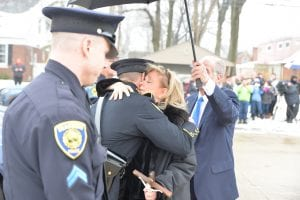 Photo by Ian Kushnir U.S. Rep. Debbie Dingell hugs a Dearborn police officer on her way into the Church of the Divine Child for the funeral of her husband, former U.S. Rep. John Dingell Feb. 12.