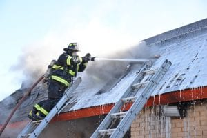 Photo by Ian Kushnir A Dearborn firefighter works to put out a fire at Wing Fingers, 5901 Schaefer Road, March 16.