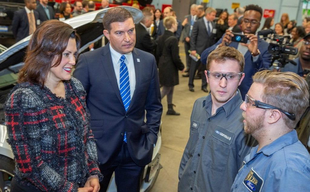 Photo courtesy of Lance Rosol/Henry Ford College Gov. Gretchen Whitmer (left) and Henry Ford College President Russell Kavalhuna speak to two students in HFC's Automotive Student Service Educational Training lab.