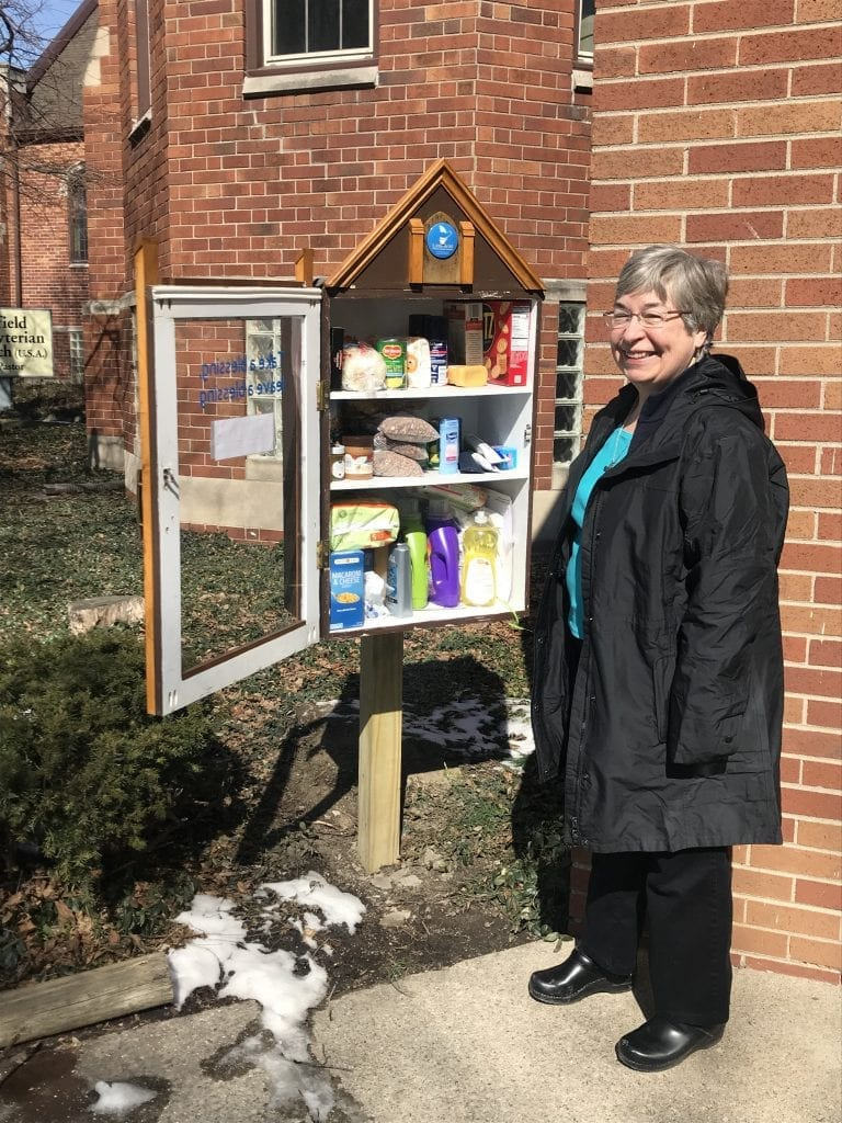 """Photo by Zeinab Najm  The Rev. Fran Hayes, pastor at Littlefield Presbyterian Church, 7560 Littlefield Blvd. in Dearborn, checks on the blessing box that stands outside the church. The blessing box is filled with items available free of charge for those in need. The idea for the box was suggest by several members of the congregation as a way to offer food, hygiene and other items to neighbors. The outside of the box reads, """"Take a blessing, leave a blessing,"""" serving as a resource for people who need the items and a place for people to donate items. Parishioner Ben Hylkema built the box and Littlefield's Misson & Outreach Team Chairwoman Anna Dewey coordinates the blessing box effort."""