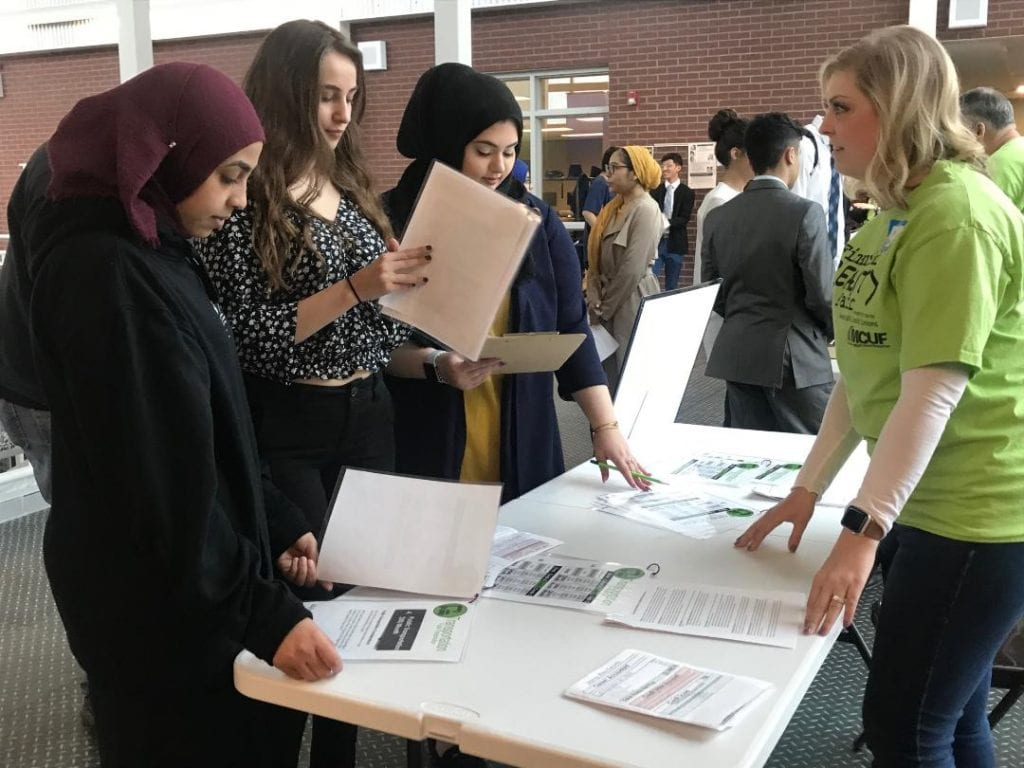Photo by Zeinab Najm Dearborn Public Schools students Gaidah Saeed (left), Alexis Bazzi and Nora Allabbah learn about the best transportation option for their created budget based on the income from their chosen career from Parkside Credit Union Chief Development Officer Heather Colonius during the Financial Reality Fair March 14 at Michael Berry Career Center.