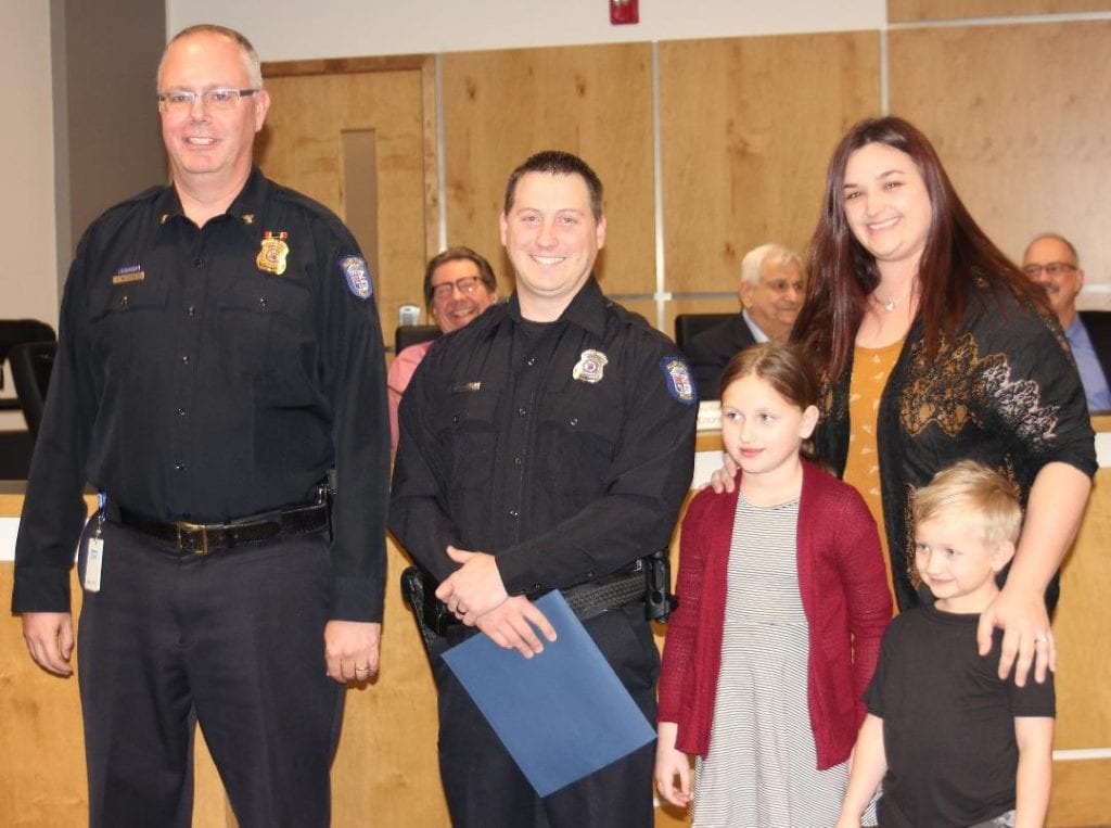 Photo by Sue Suchyta Allen Park Police Chief James Wilkewitz (left) congratulates newly sworn-in Police Officer Jared Knudsen at the March 12 City Council meeting, with his daughter, Alexis, 7; wife, Lauren; and son, Carrson, 5.