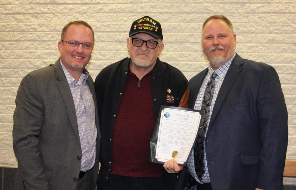 """Photo by Sue Suchyta Taylor Mayor Rick Sollars (left) and Taylor City Council Chairman Tim Woolley (right) honor longtime resident and volunteer John """"Jack"""" Myers, at the March 19 council meeting."""