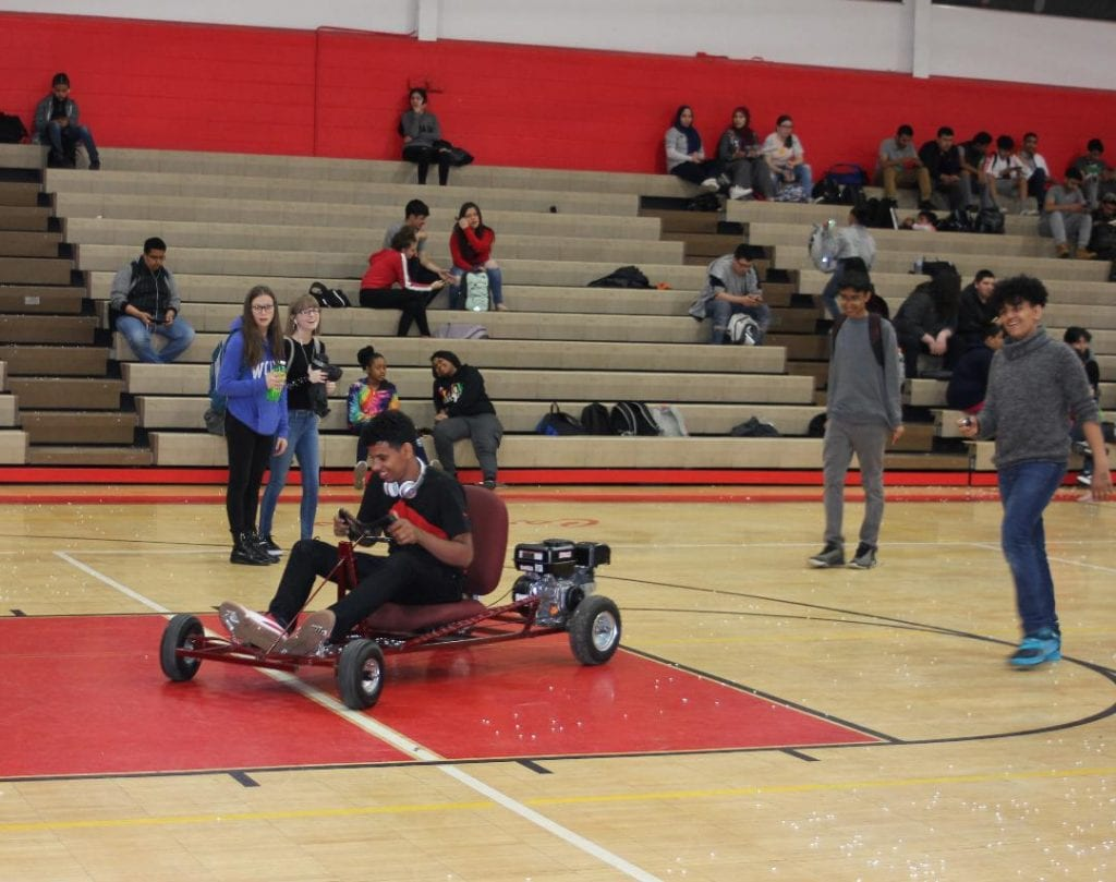 Photo by Sue Suchyta Melvindale High School senior Halzeh Aldora (front) takes a test drive in the MHS gym April 17 during the annual MHS Engineering Day.