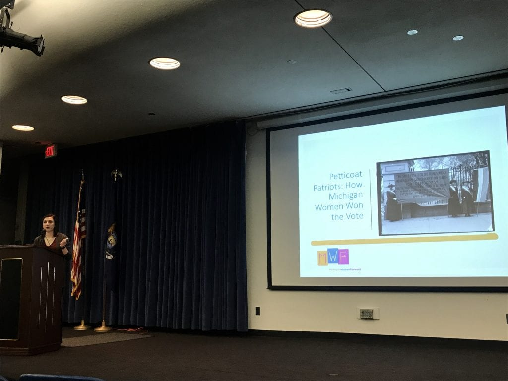 """Photo by Zeinab Najm Michigan Women Forward Lead Guest Assistant Riley Hubbard explains the history of women's voting rights in Michigan during the presentation """"Petticoat Patriots: How Michigan Women Won the Vote"""" April 17 at Henry Ford Centennial Library."""