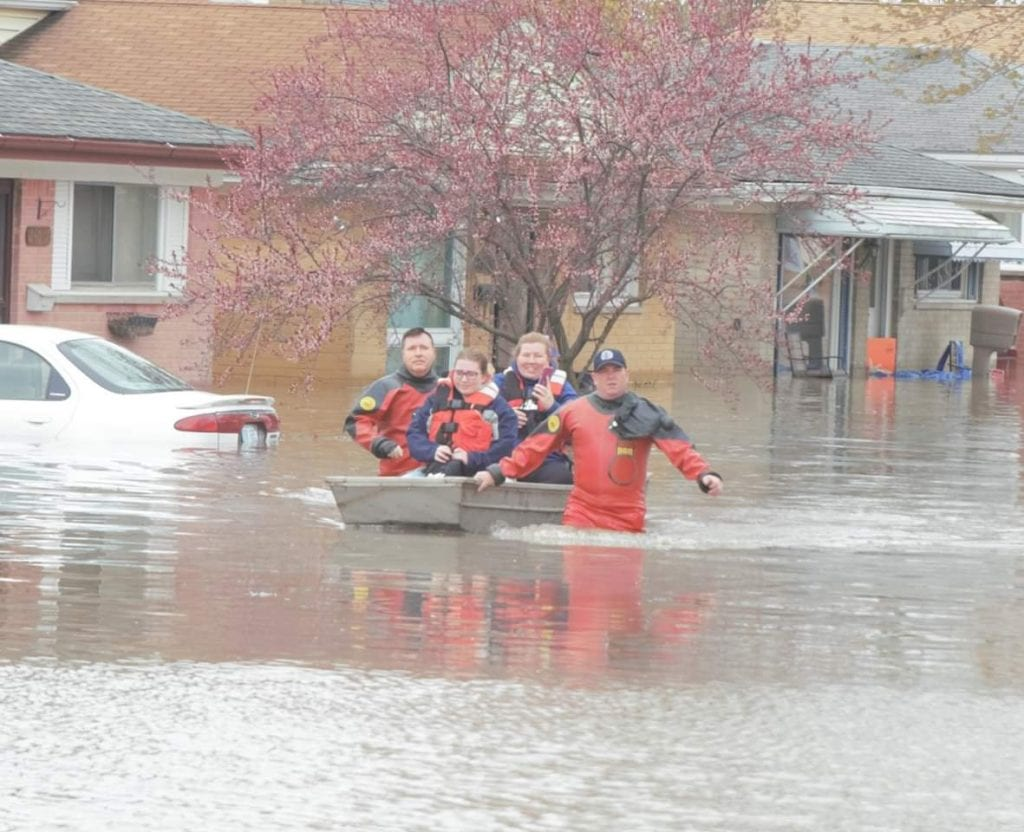 Photo by Ian Kushnir Dearborn Heights firefighters help rescue a family from their flooded neighborhood May 1 following a heavy rainfall in the area April 30.