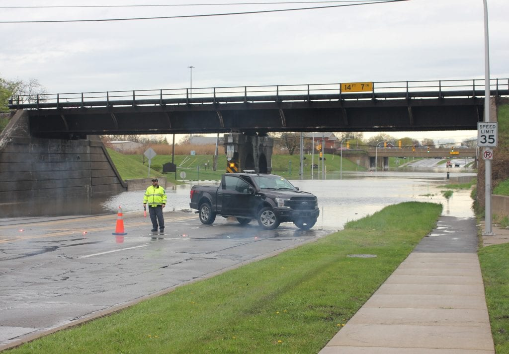 Photo by Sue Suchyta Allen Park/Melvindale Community Emergency Response Team member Mike Flanagan helps deter motorists from entering the floodwaters near Baker College, at Outer Drive east of I-94 in Allen Park May 1, after area flooding forced the closure of the campus, and the nearby road mimicked lakefront living. Almost 4 inches of rain overnight from April 30 to May 1 resulted in flooding in many areas Downriver, resulting in the closing of several roads, including Telegraph Road between Van Born and Ecorse roads, and Southfield Road under Outer Drive at the Allen Park-Dearborn-Dearborn Heights border.