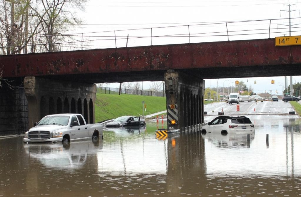 Photo by Sue Suchyta Disabled vehicles sit in flood waters on Greenfield Road in Dearborn north of the post office May 1.