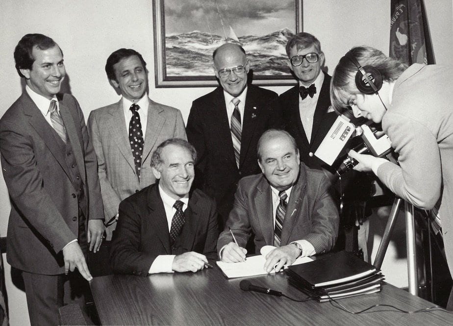 Photo courtesy of the city of Dearborn Dearborn Mayor John O'Reilly Sr. (front row second from left) signs the contract bringing cable television to Dearborn while Russ Gibb (back row right) and Group W executives watch.